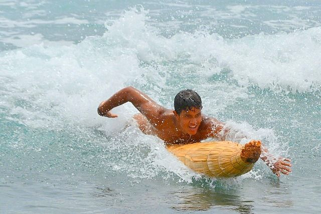 A young man rides a pora in the Hanka Ngaru competition Tapati Festival Easter Island